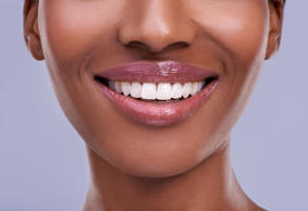 Cropped shot of a young woman's mouth against a purple background