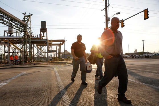 a man is walking down the street: Steel workers return to work at U.S. Steel Granite City Works in Granite City