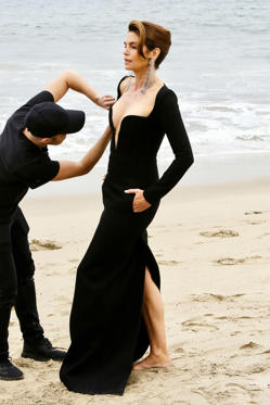 Slide 1 of 135: Cindy Crawford gets glam in a slinky black gown during a photo shoot on the beach in Malibu on Thursday.