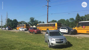 a yellow school bus parked in front of a car: Middle schooler detained in Noblesville, Indiana, school shooting