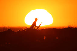 A surfer pulls off a wave as the sun sets in Cardiff during what local media reported to be a record breaking heat wave in Southern California, U.S., October 24, 2017.     REUTERS/Mike Blake