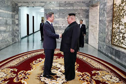 a person in a suit standing in front of a building: n this handout image provided by South Korean Presidential Blue House, South Korean President Moon Jae-in (L) shake hands with North Korean leader Kim Jong Un (R) before their meeting on May 26, 2018 in Panmunjom, North Korea. North and South Korean leaders hold the surprise second summit, after U.S. President Donald Trump once cancelled the meeting with Kim Jong-un scheduled on June 12, though Mr. Trump indicated that the meeting could take place a day after.