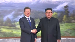 a man wearing a suit and tie: Korean leaders hold surprise meeting