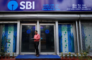 A man checks his mobile phones in front of State Bank of India (SBI) branch in Kolkata, India, February 9, 2018. REUTERS/Rupak De Chowdhuri