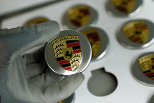 An employee of German car manufacturer Porsche displays a badge depicting a Porsche logo at the Porsche factory in Stuttgart