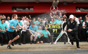 Mercedes' Lewis Hamilton and Valtteri Bottas are sprayed with champagne by a member of their team as they celebrate after finishing first and second respectively
