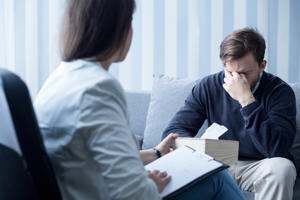 Professional counsellor helping depressed man