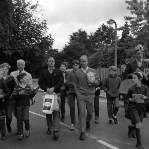With the inevitable entourage of autograph seekers, England's Bobby Charlton (right) and Ray Wilson return to their Hendon, London, hotel after a shopping expedition a few hours before the World Cup Final.   (Photo by PA Images via Getty Images)