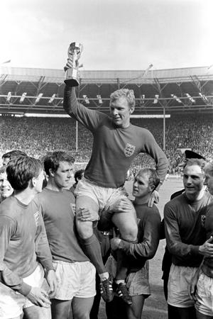 England captain Bobby Moore holds the World Cup aloft as he is chaired by his jubilant teammates: (l-r) Martin Peters, Geoff Hurst, Moore, Ray Wilson, George Cohen, Bobby Charlton   (Photo by PA Images via Getty Images)