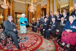 The Queen is given a book by Peter Norton as other VC and GC holders look on (John Stillwell/PA)
