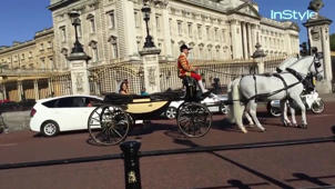 a horse drawn carriage in front of a building: Right Now: Prince Harry and Meghan Markle Dopplegangers Around London