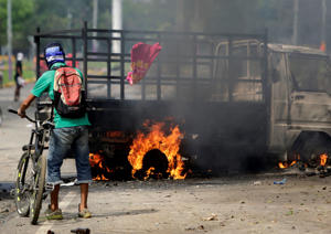A man walks by a burnt truck during protests in Masaya, some 40km southeast of Managua on May 15, 2018. - Nicaragua's powerful Roman Catholic bishops announced they are engaging in talks to resolve a crisis that has left at least 51 people dead in the wake of a crackdown on anti-government protests, initially over proposed cuts to social security benefits that have since been scrapped. (Photo by INTI OCON / AFP)        (Photo credit should read INTI OCON/AFP/Getty Images)