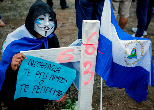A student wearing a Guy Fawkes mask holds a sign reading 'Nicaragua, we will fight for you or we will lose you' as he takes part in a protest against the government of Nicaraguan President Daniel Ortega in Managua on May 15, 2018. - Ortega will attend long-awaited crisis talks with the opposition after nearly a month of violence that has left scores dead, officials said Tuesday. (Photo by DIANA ULLOA / AFP)        (Photo credit should read DIANA ULLOA/AFP/Getty Images)