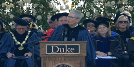 a group of people standing in front of a crowd: Tim Cook's not-so-subtle shade in Duke graduation speech