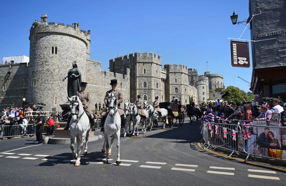 Slide 1 of 12: Here's the carriage processional leaving Windsor Castle, passing by the statue of Queen Elizabeth.