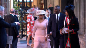 a group of people standing on a sidewalk: Oprah Winfrey, Idris Elba among first to arrive for royal wedding