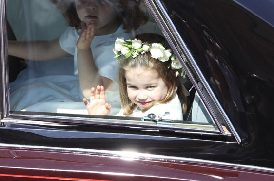 Slide 1 of 50: A flower girl waves to the crowd as she rides in a car to the wedding at St George's Chapel in Windsor Castle of Prince Harry and Meghan Markle.