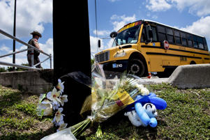A Texas State Trooper opens a gate for a bus of students and others returning to Santa Fe High School to recover their things a day after a mass shooting May 19, in Santa Fe, Texas.