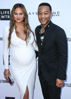 Chrissy Teigen, John Legend are posing for a picture: Chrissy Teigen and John Legend arrive at the Daily Front Row Fashion Awards in Los Angeles on April 8, 2018.