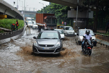 Vehicles drive through a flooded stretch of a road under the busy Hebbal flyover after a heavy downpour in Bangalore on October 5, 2017.  / AFP PHOTO / MANJUNATH KIRAN        (Photo credit should read MANJUNATH KIRAN/AFP/Getty Images)