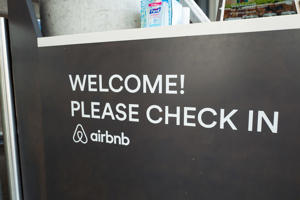 Sign with message reading 'Please Check In' at the headquarters of short-term rental technology company Airbnb in the South of Market (SoMa) neighborhood of San Francisco, California, October 13, 2017. SoMa is known for having one of the highest concentrations of technology companies and startups of any region worldwide.