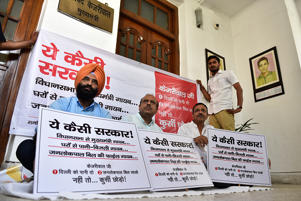 eader of Opposition in Delhi Assembly Vijendra Gupta(C) with other BJP MLAs Manjinder Singh Sirsa(L) and Jagdish Pradhan(R) hold placards during a protest against Delhi CM Arvind Kejriwal