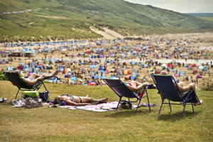 People relax in sunny weather at Woolacombe, North Devon, as the hot weather continues across the UK.   (Photo by Ben Birchall/PA Images via Getty Images)