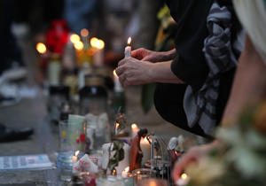 People place candles at the memorial wall on Bramley Road, London, as they attend a vigil to mark four weeks since the Grenfell Tower fire.