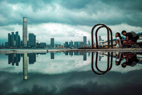 Slide 1 of 36: A couple (R) and the International Commercial Centre, (L), are reflected in a puddle as she sits on a mooring bit at a pier, Hong Kong, China, 08 June 2018. Hong Kong Observatory cancelled typhoon signal No one as tropical storm Ewiniar was moving away from the city. The International Commercial Centre is reflected in a puddle, Hong Kong, China - 08 Jun 2018