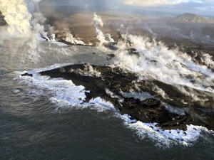 This photo provided by the U.S. Geological Survey shows new land formed by lava from KIlauea Volcano where the bay and village of Kapoho once stood on the island of Hawaii Wednesday, June 13, 2018. The new coastline, following the ragged lava-ocean interface, is approximately 2.1 kilometers (1.3 miles) in length. The white steamy laze plume marks the location of the most active lava entry site.
