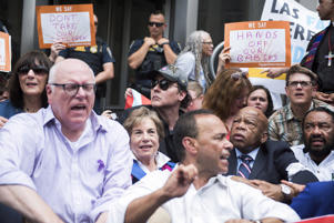 From left, Reps. Joe Crowley, D-N.Y., Jan Schakowsky, D-Ill., actor John Cusack, Luis Gutierrez, D-Ill., John Lewis, D-Ga., Al Green, D-Texas, and others sit on the 14th Street NW, entrance to the U.S. Customs and Border Protection in protest of the Trump Administration's policy of separating parents and children at the border on June 13, 2018.