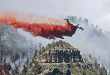 An aircraft makes a fire retardant drop on a wildfire in the mountains and forests near Durango, Colo