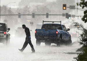 File Photo: A man crosses during a heavy rainfall in Colorado