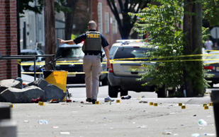 A police officer stands in a lot near evidence markers outside the warehouse building where the Art All Night Trenton 2018 festival was the scene of a shooting that resulted in numerous injuries and at least one death Sunday, June 17, 2018, in Trenton, N.J.