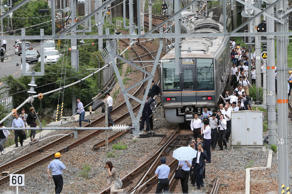 Passengers from a train walk along railroad tracks following an earthquake in Osaka on June 18, 2018.