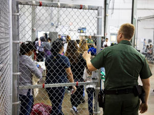 A U.S. Border Patrol agent watches as people who've been taken into custody related to cases of illegal entry into the United States, stand in line at a facility in McAllen, Texas, Sunday, June 17.