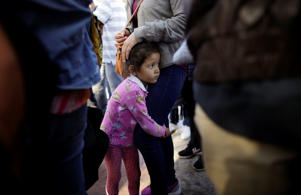 In this June 13, 2018 photo, Nicole Hernandez, of the Mexican state of Guerrero, holds on to her mother as they wait with other families to request political asylum in the United States, across the border in Tijuana, Mexico. The family has waited for about a week in this Mexican border city, hoping for a chance to escape widespread violence in their home state.
