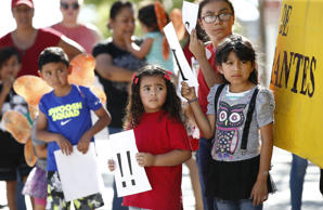 Children listen to speakers during an immigration family separation protest in front of the Sandra Day O'Connor U.S. District Court building, Monday, June 18, 2018, in Phoenix.