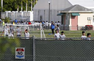Immigrant children play outside a former Job Corps site that now houses them, Monday, June 18, 2018, in Homestead, Fla. It is not known if the children crossed the border as unaccompanied minors or were separated from family members. An unapologetic President Donald Trump defended his administration's border-protection policies Monday in the face of rising national outrage over the forced separation of migrant children from their parents.