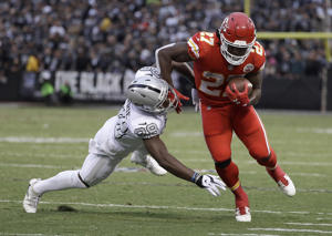 Kansas City Chiefs running back Kareem Hunt (27) is forced out of bounds by Oakland Raiders cornerback T.J. Carrie during the first half of an NFL football game in Oakland, Calif., Thursday, Oct. 19, 2017.