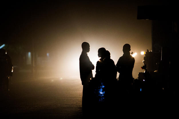 Migrants walk towards the bus station in Agadez, Niger as the lights of a bus arriving from the capital Niamey illuminate the road into this city at the southern edge of the Sahara desert.