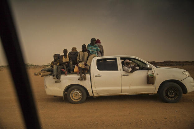 A pick-up truck filled with migrants returns to the city of Agadez after it was turned back by military checkpoints in the Sahara desert.