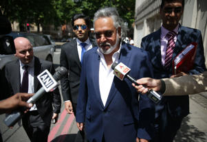 Indian tycoon Vijay Mallya is mobbed by members of the press as he leaves court in central London on June 13, 2017. Mallya appeared in court to fight an extradition request from India where he is accused of fraud. / AFP PHOTO / Daniel LEAL-OLIVAS        (Photo credit should read DANIEL LEAL-OLIVAS/AFP/Getty Images)