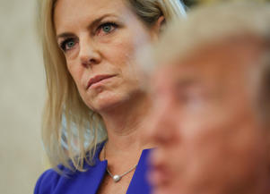 Homeland Security Secretary Kirstjen Nielsen, left, listens to President Donald Trump, right, speaks to members of the media after Trump signed an executive order to end family separations, during an event in the Oval Office of the White House in Washington, Wednesday, June 20, 2018.