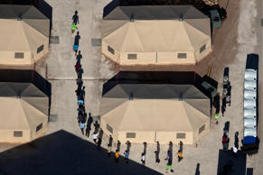 Immigrant children are led by staff in single file between tents at a detention facility next to the Mexican border in Tornillo, Texas, U.S., June 18, 2018.