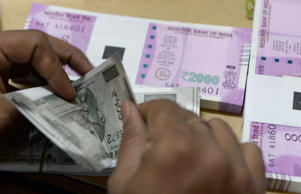 A bank staff member counts Indian 500 rupee notes to give to customers on November 24, 2016, in the wake of the demonetisation of old 500 and 1000 rupee notes in Mumbai. The US dollar hit a record high against the Indian rupee November 24 as the greenback surges on expectations of a rate hike next month following Donald Trump's shock presidential election victory. The US currency bought 68.8625 rupees during early afternoon forex trading, surpassing the previous high of 68.8450 recorded in August 2013.   / AFP / INDRANIL MUKHERJEE        (Photo credit should read INDRANIL MUKHERJEE/AFP/Getty Images)