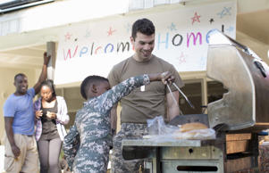 Barbecuing burgers with soldier at homecoming