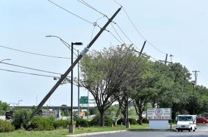 One of several power poles leans along String Line Road near 122nd Street in Olathe, Kan., after high winds from a morning storm moved through the area on Saturday, June 2, 2018.
