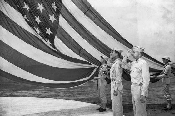 Slide 1 of 10: The garrison flag and largest in use by the U.S. Army, 20 x 38 feet - was the first flown over the fortress of Ehrenbreitstein in Germany just after World War I by the 17th Field Artillery at Camp Blanding in Florida, and shown in 1942. It was raised over the camp here in an Independence Day symbolism accentuating the United Nations' fight against Axis aggression. Brig. Gen. L.A. Kunzig, camp commander, closest to flag, and Lieutenant Col. Harry A. Johnston, camp executive, salute as the military police color guard raise it on the campground flagstaff.