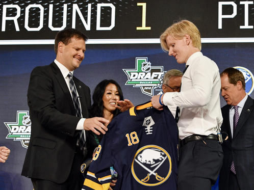 Slide 1 of 25: Jun 22, 2018; Dallas, TX, USA; Rasmus Dahlin is presented with a team jersey after being selected as the number one overall pick to the Buffalo Sabres in the first round of the 2018 NHL Draft at American Airlines Center.